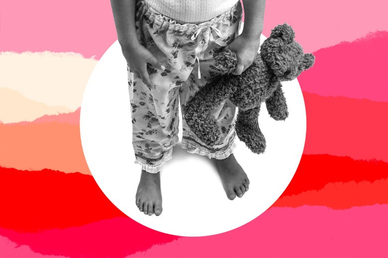 A young girl in her pajamas holding a stuffed animal.