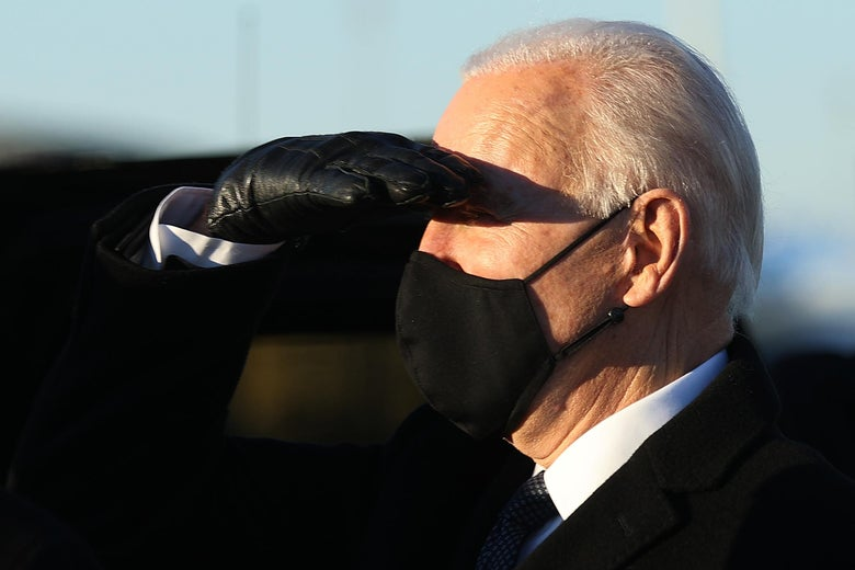 Biden, wearing a black mask, salutes with a gloved hand