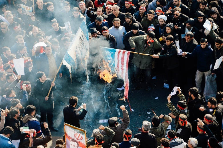 A crowd gathers around two flags on fire.