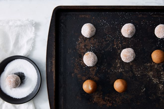 Rolled dough balls, some of which are covered in sugar.