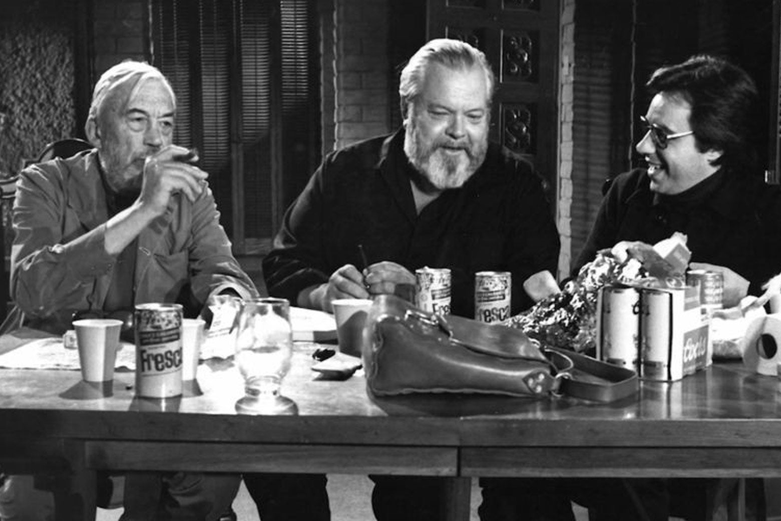John Huston, Orson Welles, and Peter Bogdanovich in a scene from The Other Side of the Wind. They're seated at a table laden with cans of Fresca. Huston is smoking.