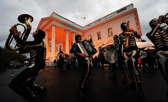 The White House is lit with orange light as a group of 'skeletons' perform.