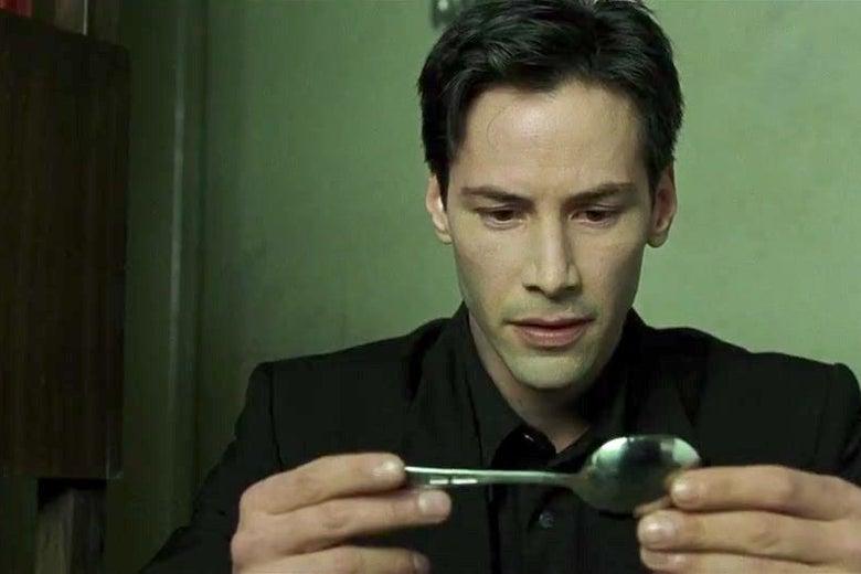 Keanu Reeves gazes at a spoon.
