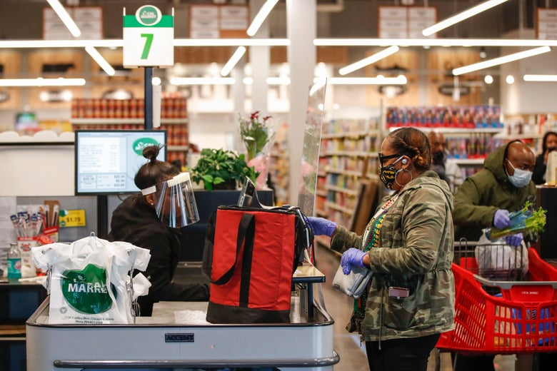 A customer wearing a face mask pays for her groceries at a store counter.