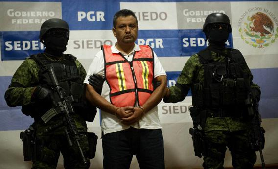 Soldiers of the Mexican Army escort Alfredo Aleman Narvaez, aka 'El Comandante Aleman', an alleged member of the drug cartel 'Los Zetas', during his presentation in Mexico City on November 17, 2011.