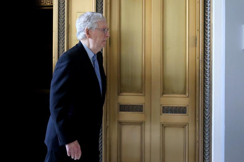 Mitch McConnell walks through a door.