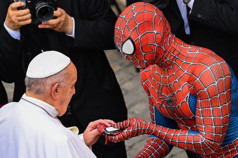 A man dressed in a Spider-Man costume hands Pope Francis a Spider-Man mask.