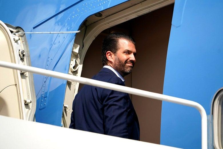 Donald Trump Jr. looks backward, smirking, as he boards Air Force One.