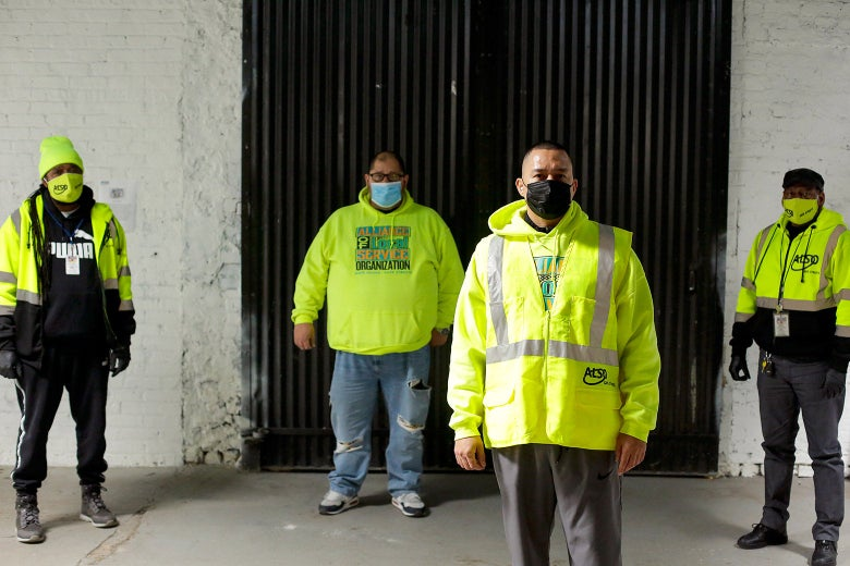 Four people wearing bright safety jackets and masks, standing a few feet apart from one another outside
