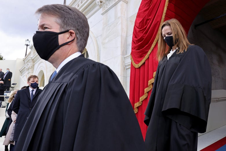 Kavanaugh and Barrett, both wearing robes and black masks, walking toward the inauguration stage at the Capitol