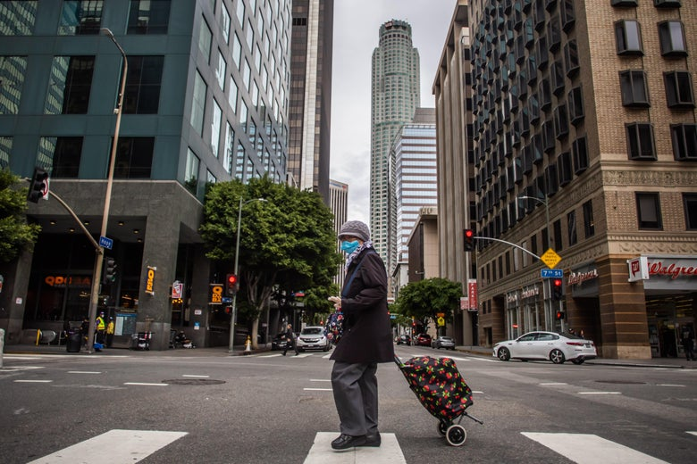 A woman wearing a mask walks in Downtown Los Angeles on March 22, 2020, during the coronavirus (COVID-19) outbreak.