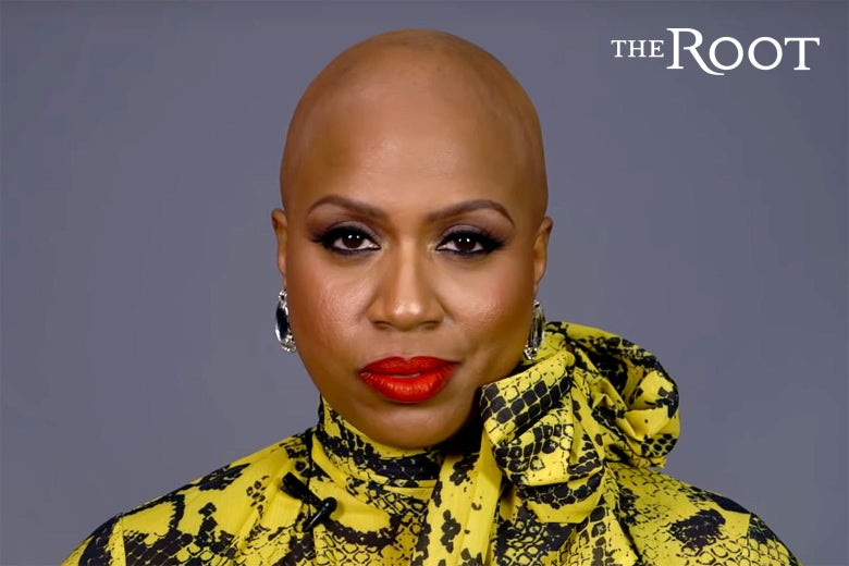 Ayanna Presley facing the camera, in a yellow and black patterned blouse, with her head fully bald.