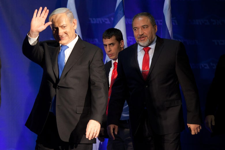 Israeli Prime Minister Benjamin Netanyahu waves to his supporters as he arrives with Former Israel Minister for Foreign Affairs Avigdor Liberman at his election campaign headquarters on Janurary 23, 2013 in Tel Aviv, Israel.