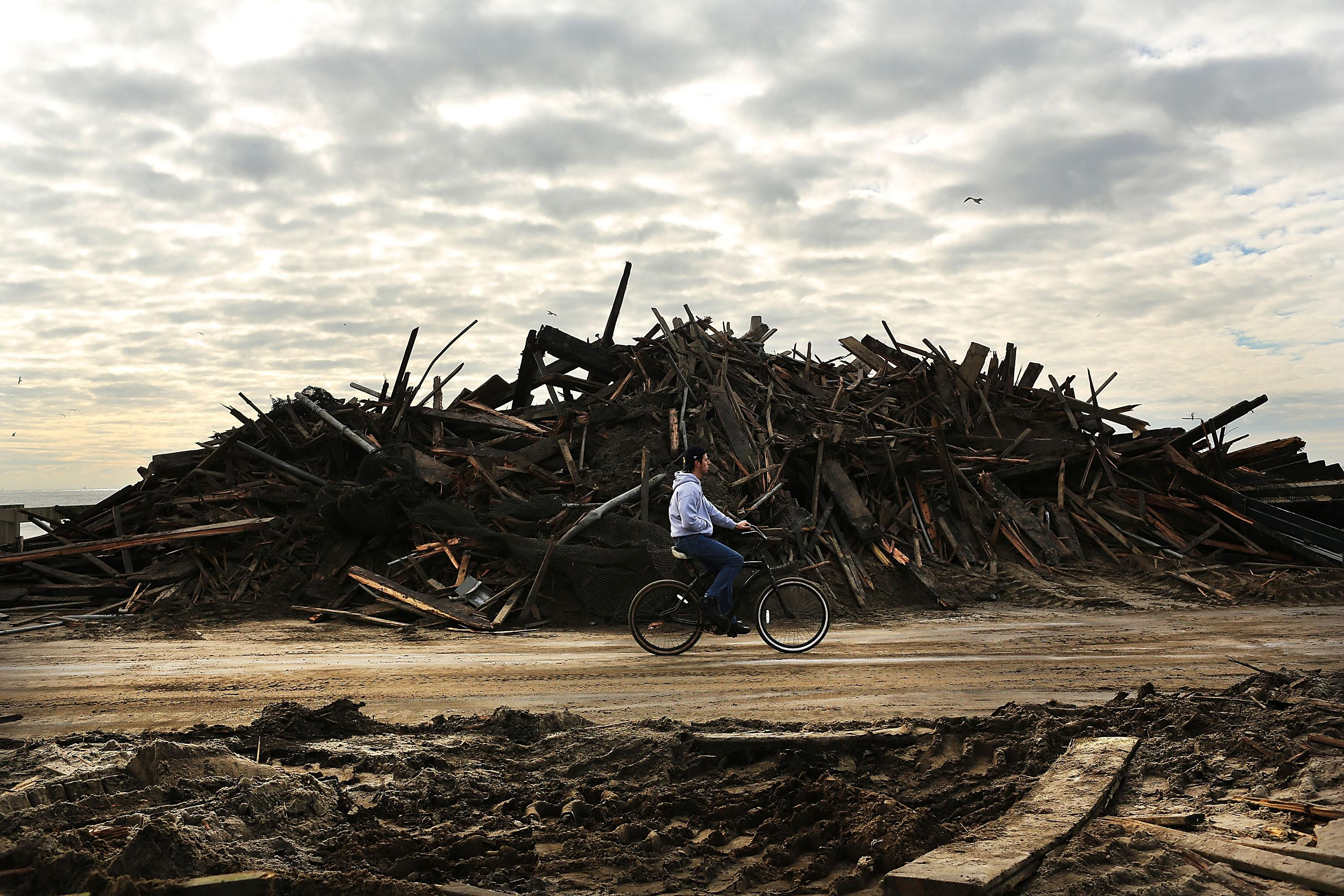 A man rides his bike through the heavily damaged Rockaway neighborhood, in Queens where a large section of the iconic boardwalk was washed away on November 2, 2012 in New York.