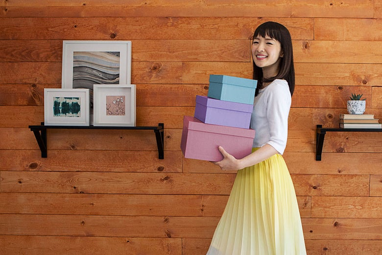 Marie Kondo smiling, carrying a neat stack of boxes, next to a wood wall with tasteful picture and plant mounts.