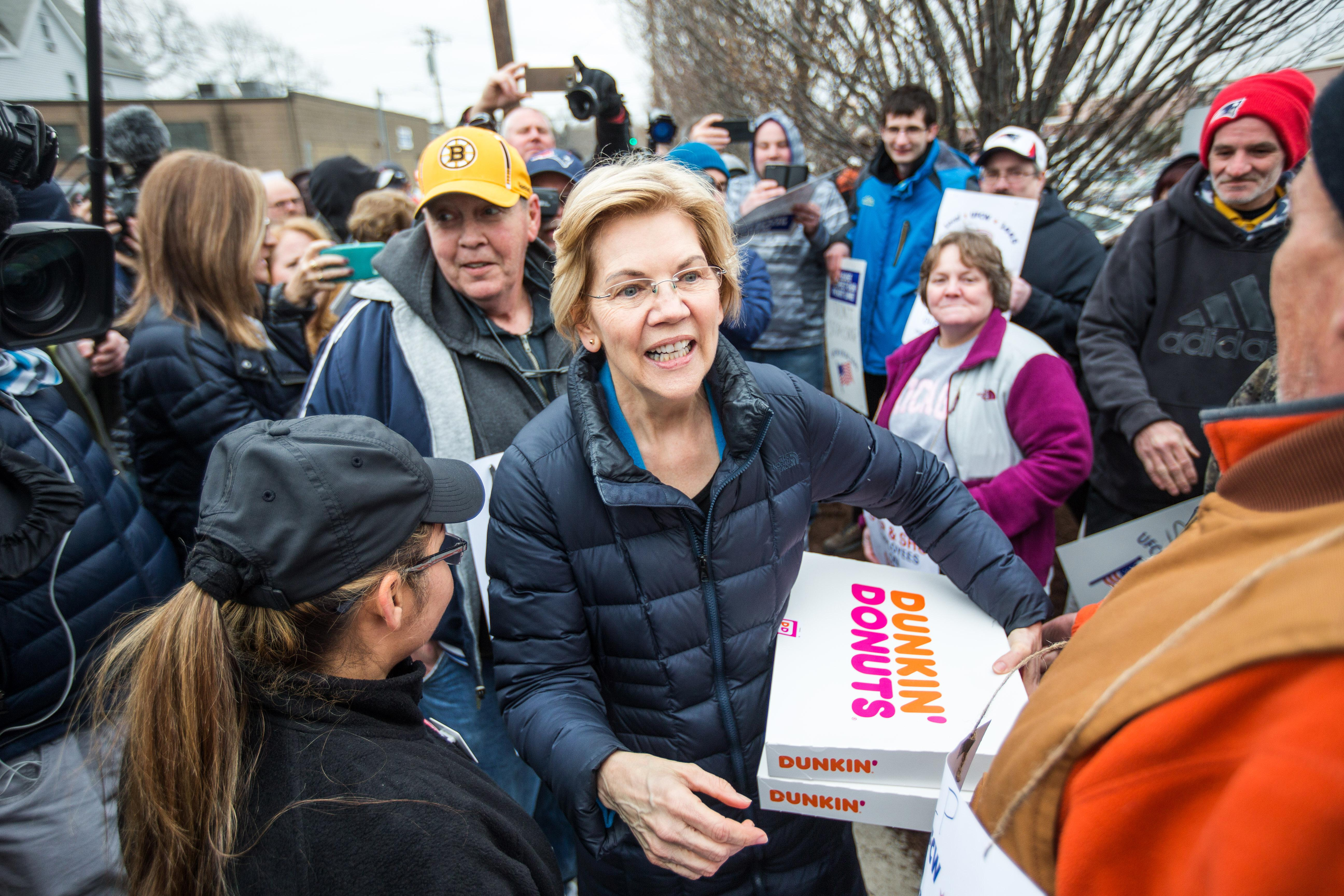 Elizabeth Warren holds two boxes from Dunkin' Donuts amid a crowd of strikers.