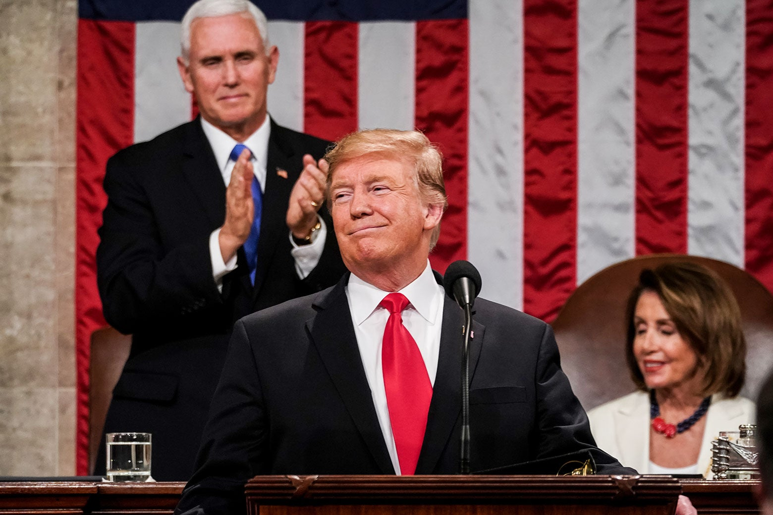 Donald Trump smiles as Mike Pence stands to applaud. Nancy Pelosi is seated and smiling.