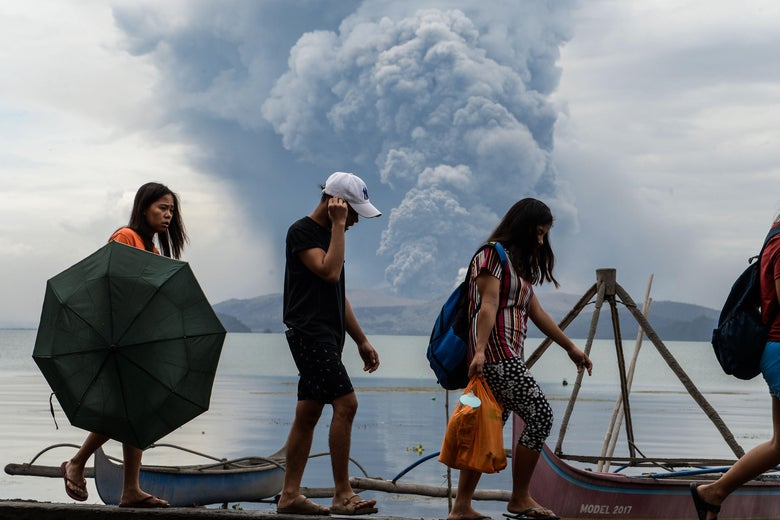 Residents holding umbrellas and carrying backpacks walk beside a body of water, with the volcano's ash column in the background.