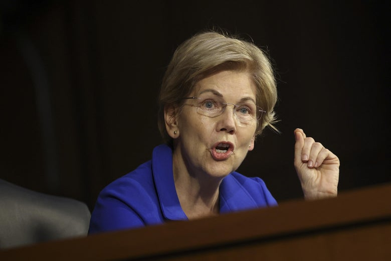 Warren holds up a clasped hand as she speaks at a hearing.