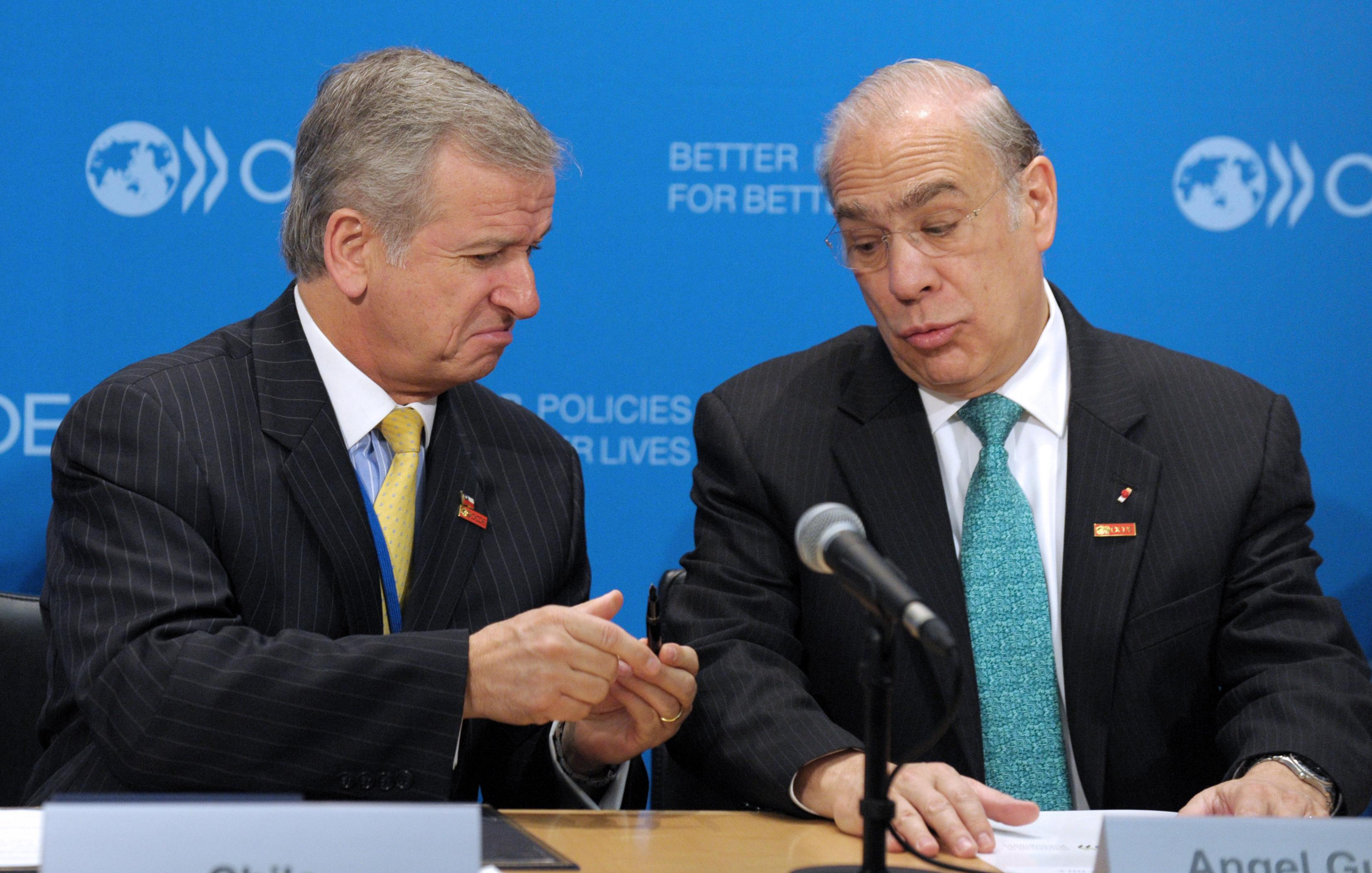 Chile Minister of Finance Felipe Larrain and OECD General Secretary Angel Gurria joke about the pen before the signing by Chile of a letter of intention to sign an OECD multilateral convention on mutual administrative assistance in tax matters during a signing ceremony at the OECD headquarters in Paris on May 29, 2013.