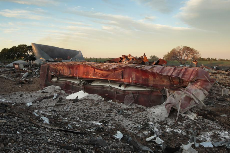 A railroad boxcar filled with ammonium nitrate lays on its side near to the remains of the fertilizer plant that exploded yesterday afternoon on April 18, 2013 in West, Texas.
