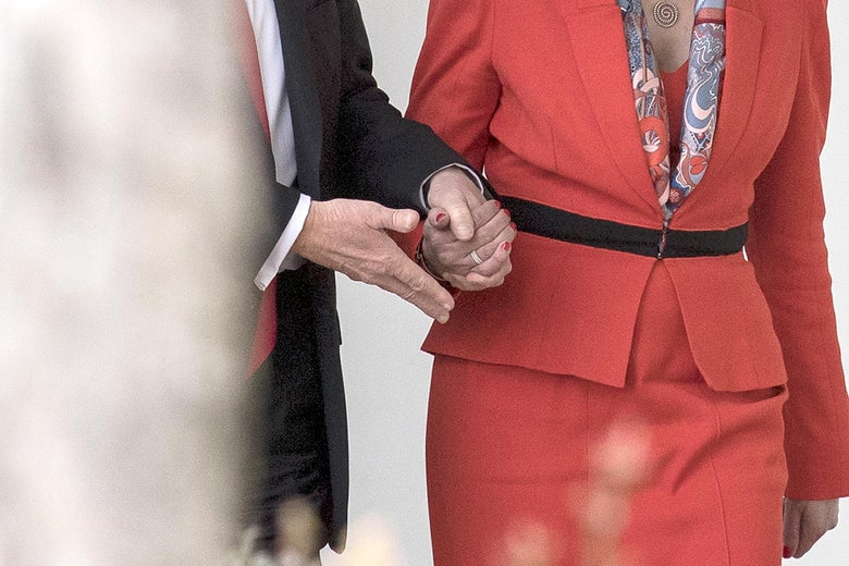 Donald Trump grasps Theresa May's hand as the two encounter a set of stairs.