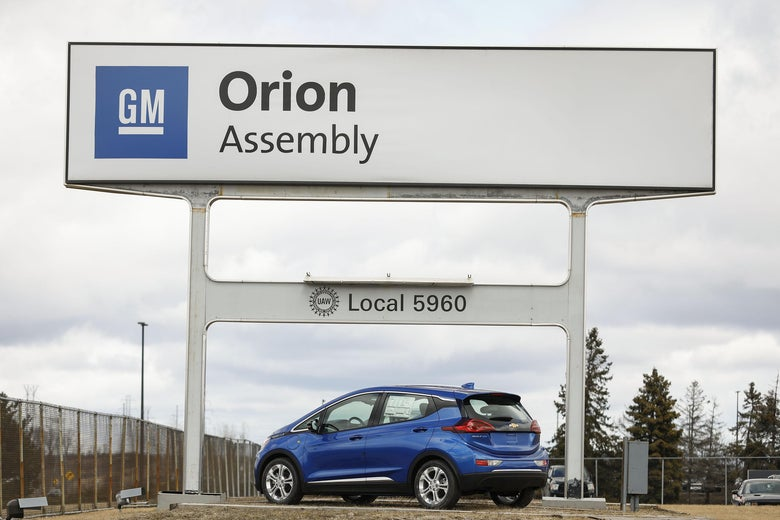 A blue electric vehicle is parked below the General Motors Orion Assembly plant sign.