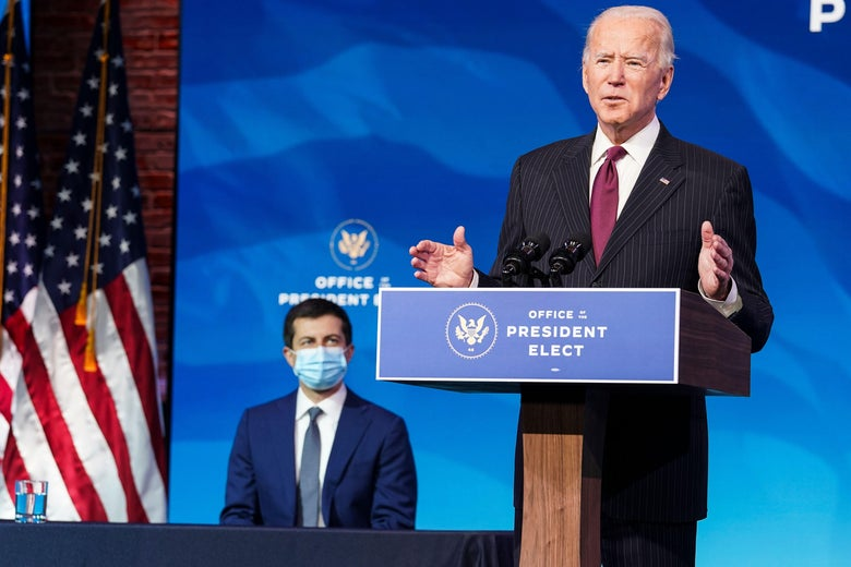 Biden speaks at a lectern while Buttigieg sits behind him, wearing a face mask.