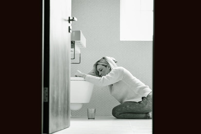 A woman kneels over the toilet in misery.