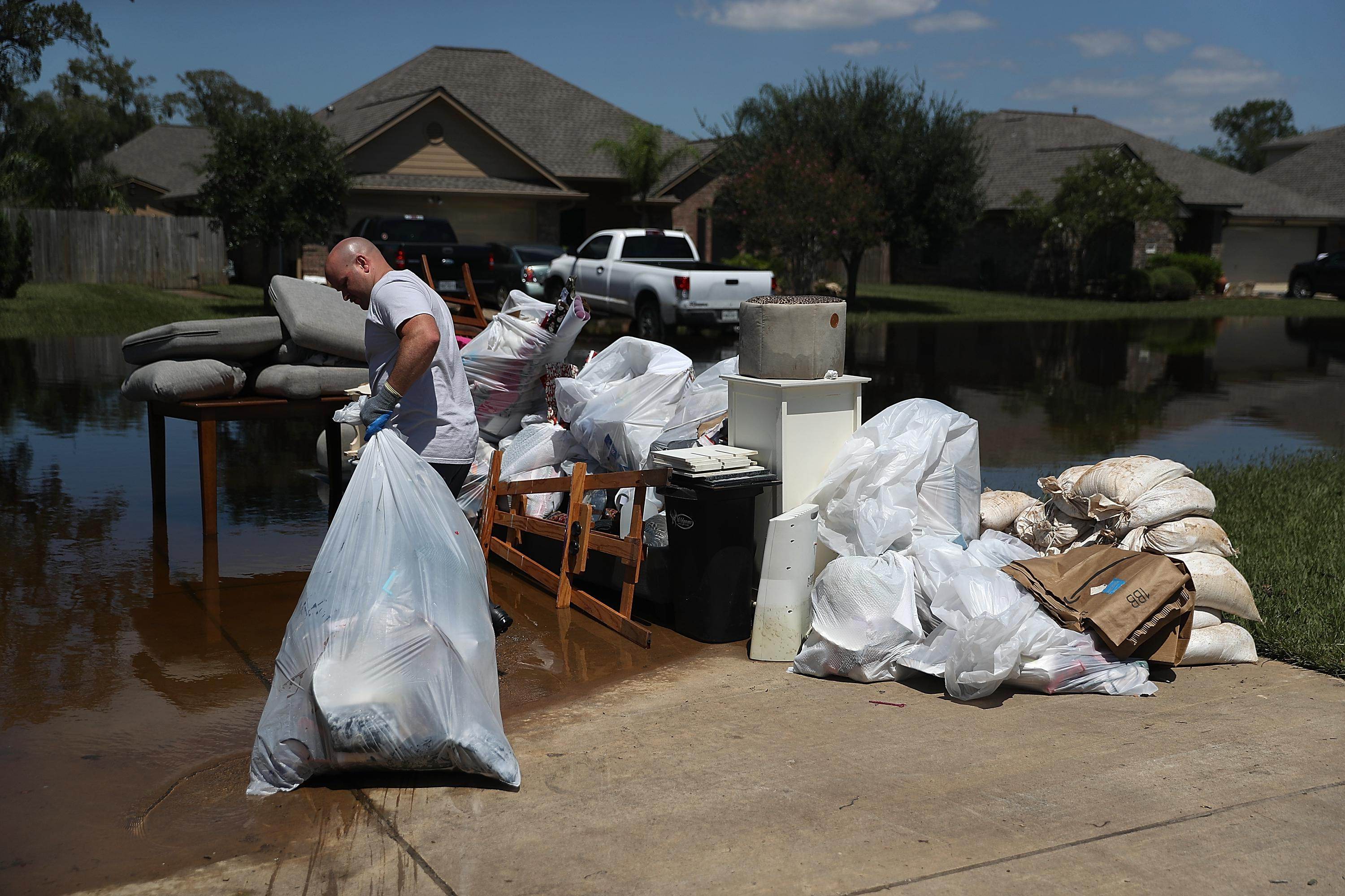 Justin Davison pulls a trash bag full of flood-damaged items to a trash pile as he helps a friend clean out his flooded home.