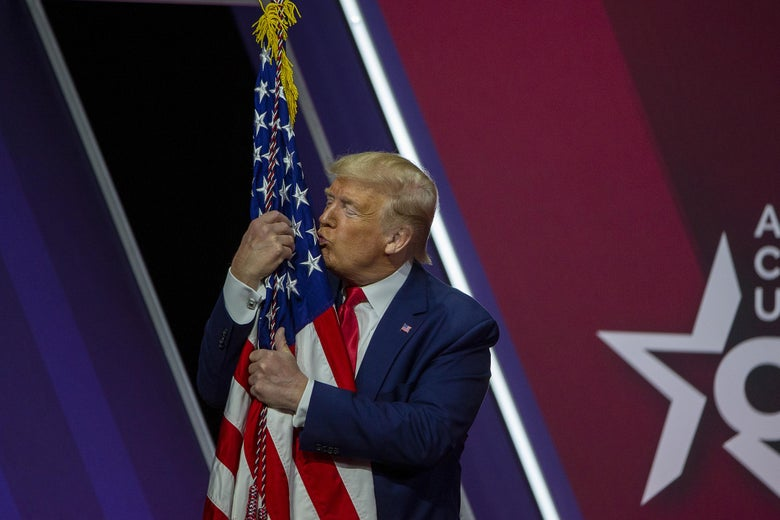 President Donald Trump kisses the flag of the United States of America at the annual Conservative Political Action Conference (CPAC) at Gaylord National Resort & Convention Center February 29, 2020 in National Harbor, Maryland.