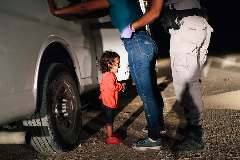 A Honduran girl cries on the ground as her mother is searched against a truck by a border patrol agent.