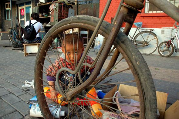 A boy plays with bottles outside his parents' bicycle shop in the student district of Wudaokou in Beijing, May 2008.