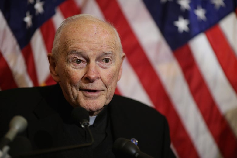 Theodore McCarrick behind microphones in front of American flags.