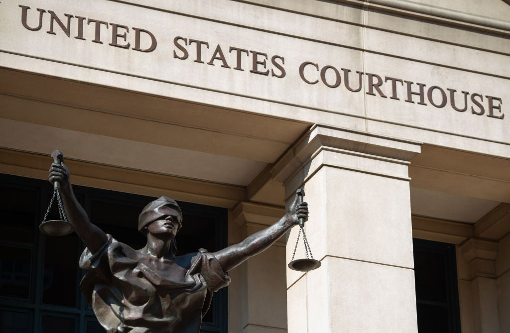 A blind-justice-holding-scales statue in front of a UNITED STATES FEDERAL COURTHOUSE sign.