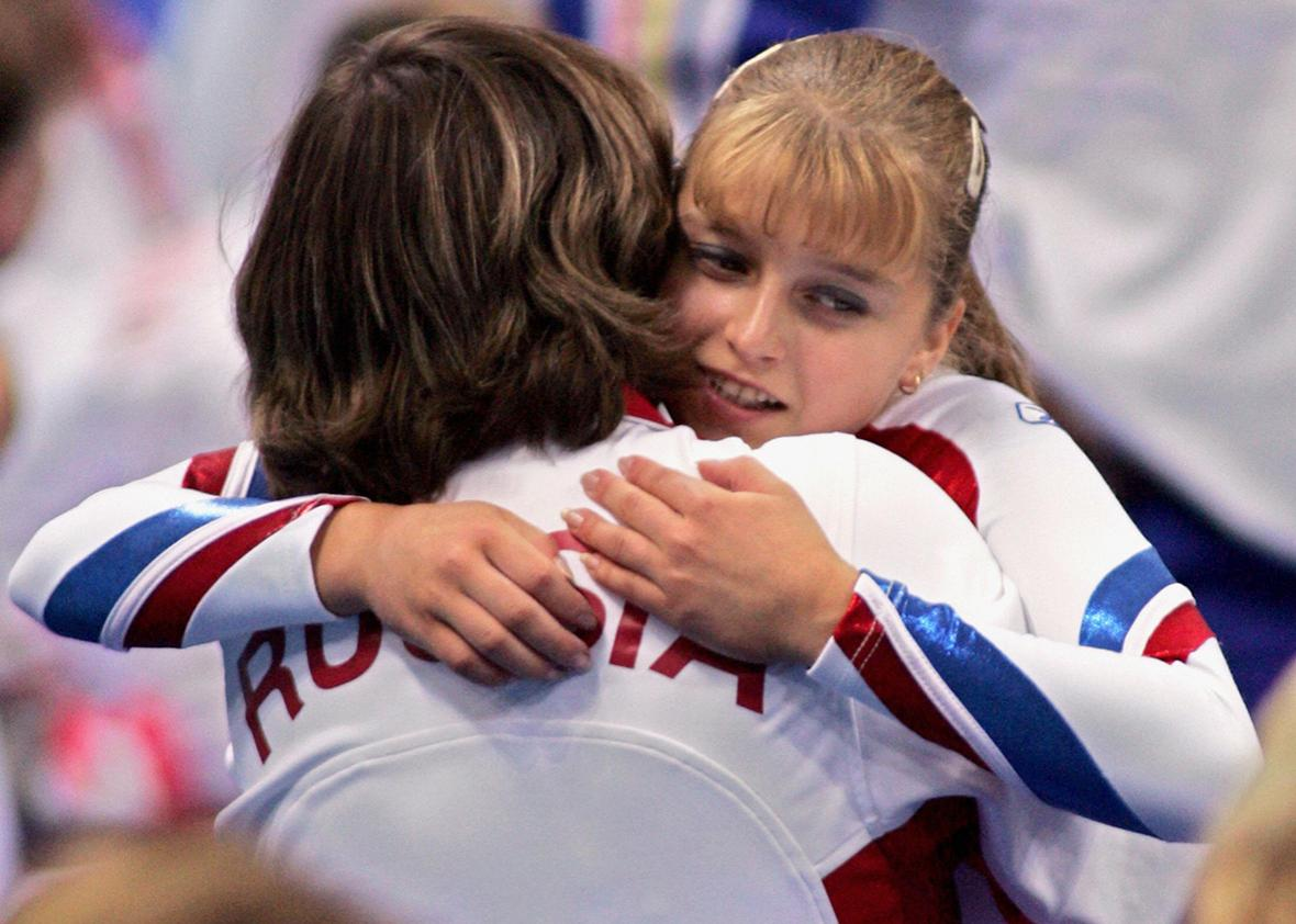 Russian Anna Pavlova is congratulated by an unindentified staff member after winning the bronze medal in the women's vault final 22 August 2004 at the Olympic Indoor Hall in Athens during the Olympics Games.