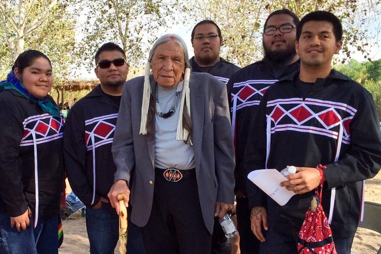 Five young Native Americans stand around an elder.