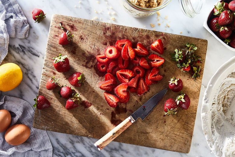 A cutting board laden with fresh, sliced strawberries.