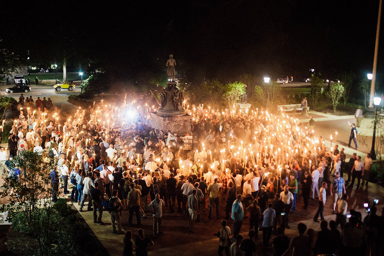 White supremacists  with torches encircle counter-protestors at the base of a statue of Thomas Jefferson
