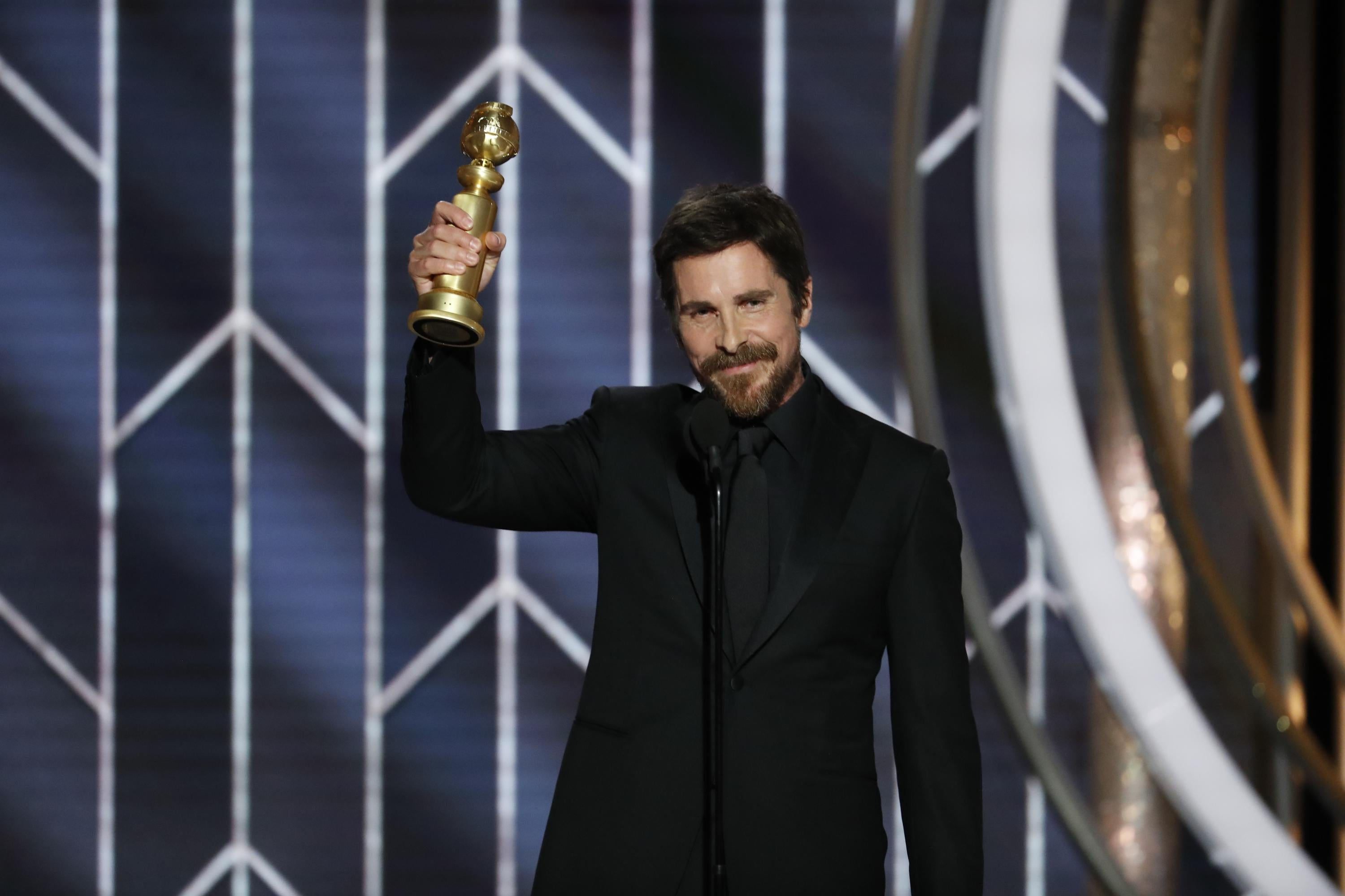 Christian Bale holding up a Golden Globe.