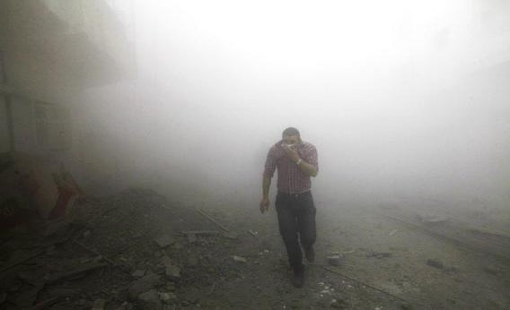 A man runs amongst rubble as smoke rises from buildings damaged by what activists said were missiles fired by a Syrian Air Force fighter jet loyal to President Bashar al-Assad in Raqqa province, eastern Syria, March 12, 2013.