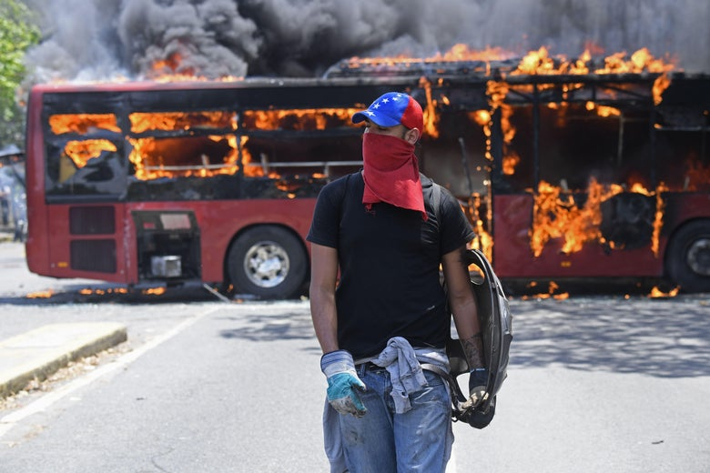 An opposition demonstrator wearing a hat and a cloth over his face walks in front of a burning bus.