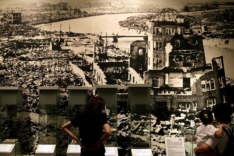 Visitors look at a picture, showing the aftermath of the atomic bomb attack on Hiroshima at the Hiroshima Peace Memorial Park in Japan.