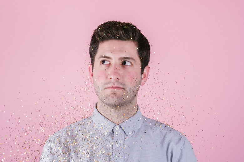 A man in a button-down shirt with glitter in the air.