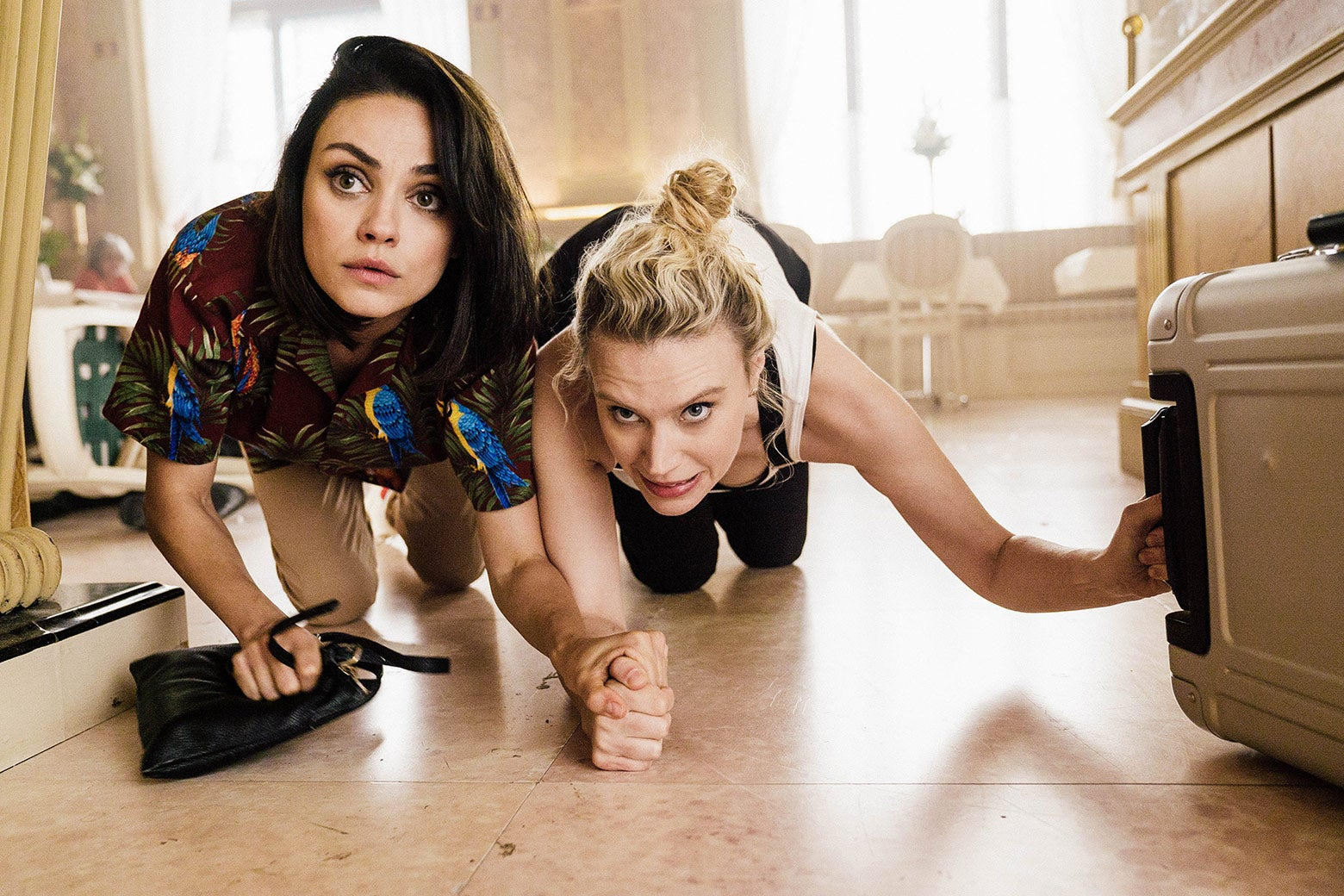 Mila Kunis and Kate McKinnon crawl on the floor in a still from the film.