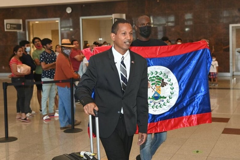 Shyne, wearing a suit, walks his suitcase while a man in a face mask behind him holds the Belize flag.