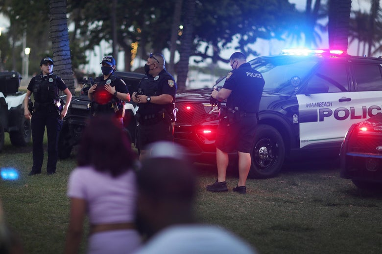 Miami Beach police officers keep an eye on people along Ocean Drive on March 19, 2021 in Miami Beach, Florida.