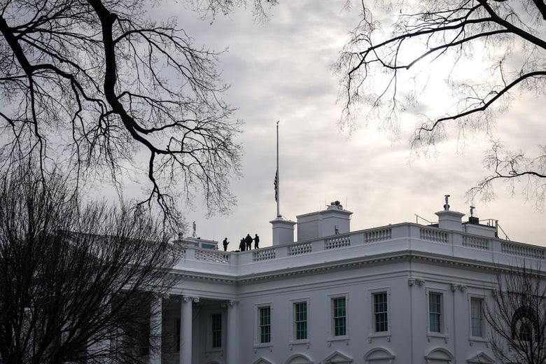 A flag at half-mast is seen above the upper floor of the White House against bare trees and a gray sky.