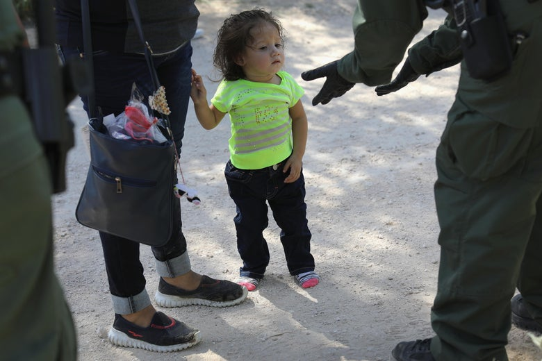 A toddler holds the hand of an adult as a uniformed Border Patrol officer approaches with gloved hands outstretched.