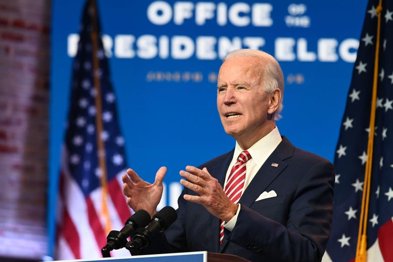 """Joe Biden stands at a lectern in front of American flags and a sign that says """"U.S. President Elect."""""""